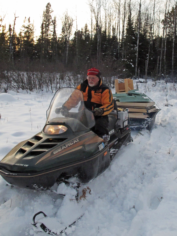 Lynn_driving_snowmobile_pulling_fish-house